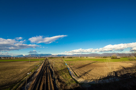 a railway through the fields in direction of mountains of Friuli Venezia-Giulia, Italy photo