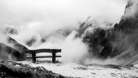 a bench on the top of an alpine valley photo