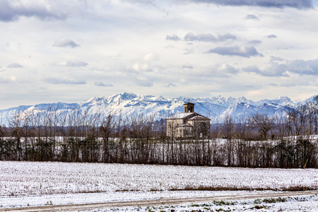 snow on the fields next to a medieval church in the italian countryside photo