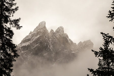 a mountain between the fog in the italian alps photo