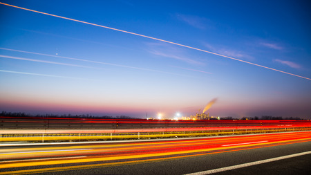 power production: sunset on the highway in front of an industry