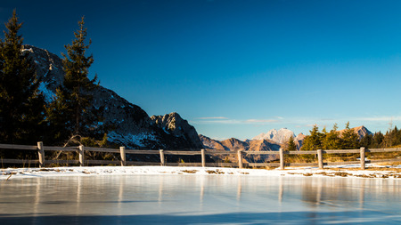 iced little lake in the italian alps in a sunny winter day Stock Photo