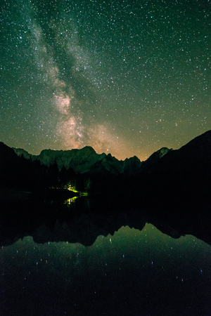The sun goes down and stars out in front of Mount Mangart in the italian alps