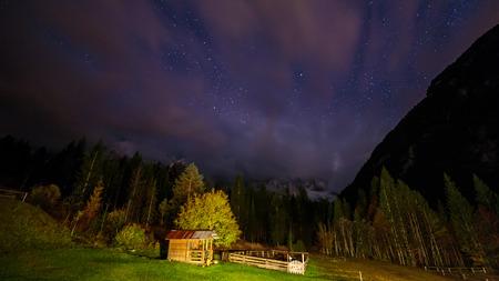 an alpine hut in the valley during a dark night