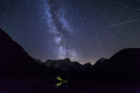 The sun goes down and stars come out in front of Mount Mangart in the italian alps