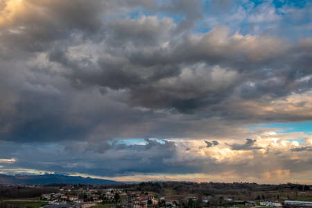 The sun goes behind the clouds over the countryside of Udine, Friuli-Venezia Giulia, Italy