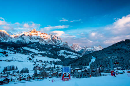 Sun goes down on an alpine valley in italy during a snowy winter