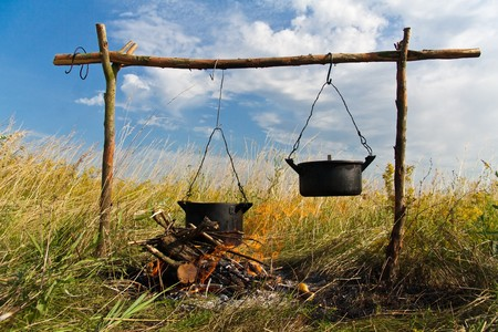 Boiling water in pots above the fire  photo