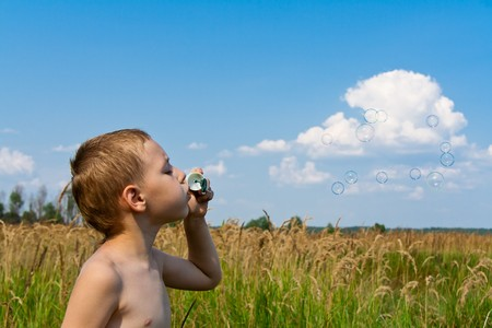 Little boy blowing soap bubbles against blue sky photo