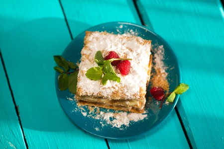 close up of Mille-feuille puff pastry with raspberries on a blue Board
