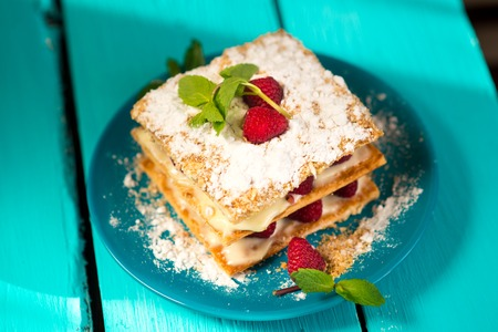 Mille-feuille of puff pastry with raspberries on a wooden Board cyan