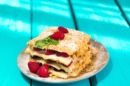 Mille-feuille of puff pastry with raspberries on a wooden Board cyan Stock Photo