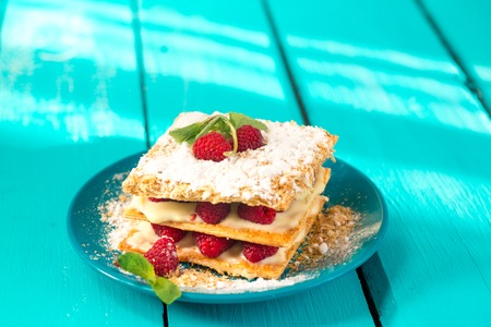 close up of Mille-feuille puff pastry with raspberries on a blue Board Stock Photo
