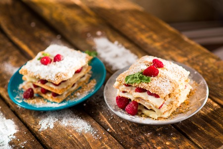 Mille-feuille of puff pastry with raspberries on a wooden Board