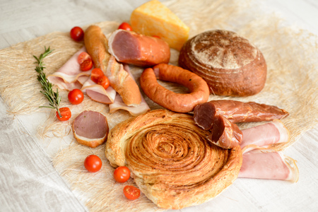 cold cuts on a wooden Board with vegetables and bread