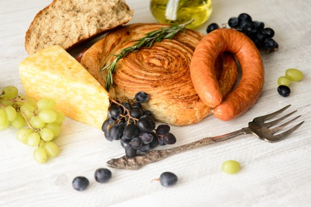 sausage,cheese,bread,grapes on a wooden Board with olive oil in the bottle
