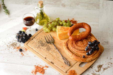 sausage,cheese,bread,grapes,a glass of red wine on wooden Board with olive oil in the bottle