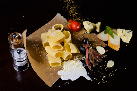 an onions: Italian food and ingredients pasta lying on the paper on a dark background