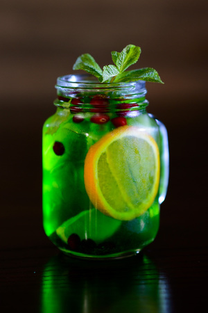 alcochol: refreshing cocktail with lime, lemon and mint on black background