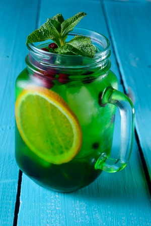 alcochol: refreshing cocktail with lime, lemon and mint on a blue background Stock Photo