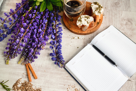 Note with a pen, a calendar and a Cup of coffee served with bruschetta, lupins flowers on wooden table