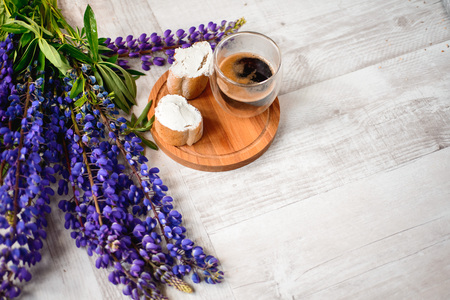 A Cup of coffee,note book , cracker, cookie, biscuit, lupins flowers on a wooden table.