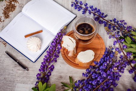 vibe: A Cup of coffee,note book , cracker, cookie, biscuit, lupins flowers on a wooden table.