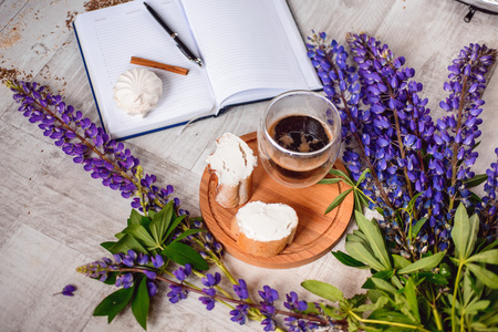 a meeting with a view to marriage: Note with a pen, a calendar and a Cup of coffee served with bruschetta, lupins flowers on wooden table