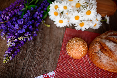 Close up on traditional bread on the table, next to flowers daisies and lupins