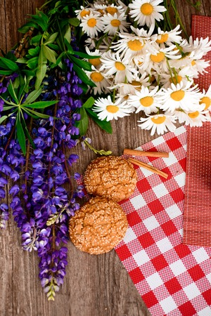 chamomile flower: Fresh bread and chamomile flowers and lupins on the garden table. On the morning of the background. The view from the top. Stock Photo