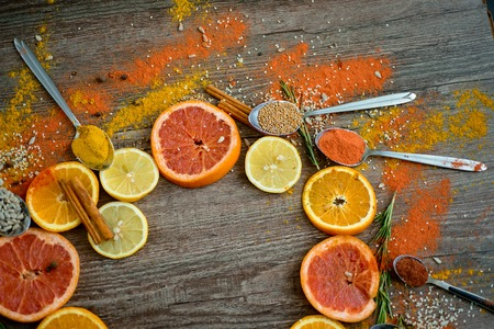the fragrance of spices, red pepper, black pepper, mustard,sunflower seeds ,and orange slices of citrus fruits on dark wooden background of the table. Closeup top view