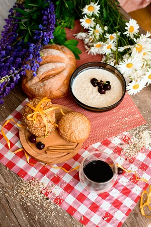 chamomile flower: coffee,oatmeal,Fresh bread and chamomile flowers and lupins on the garden table. On the morning of the background. The view from the top. Stock Photo