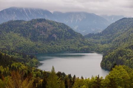 Germany, the Alpsee Lake, surrounded by hilly terrain Stock Photo