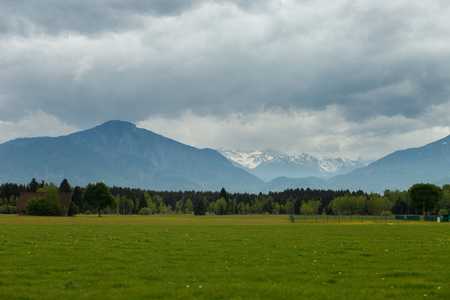 landscape in the Alps with fresh green meadows and snow-capped mountain peaks in the background, Bavaria, Germany