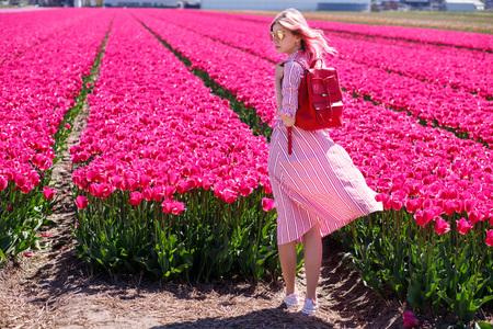 Smiling teenage girl walks through tulip field.Holland