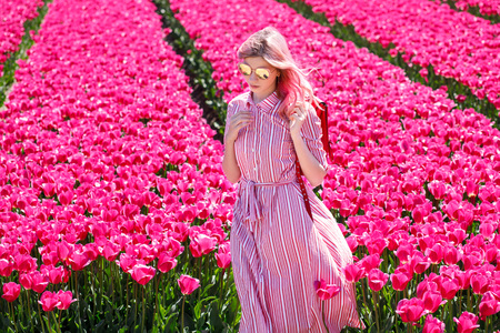 Smiling teenage girl walks through tulip field.Holland