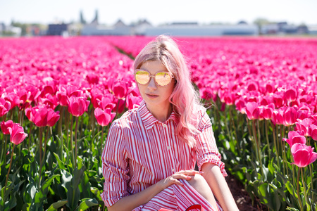 Smiling teenage girl walks through tulip field.Holland Archivio Fotografico - 115532868