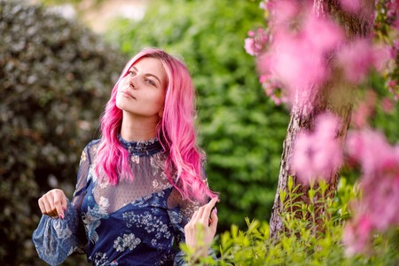 young beautiful girl with pink hair standing near a tree with flowers, pink flowers, spring, sun, happiness, tenderness Archivio Fotografico - 115534680