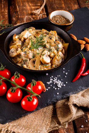 Mushrooms in cream sauce, julienne. Champignon on a black slate background on a wooden table