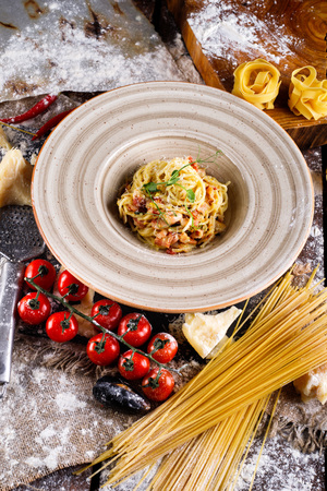 Pasta Carbonara with Parmesan cheese and sauce on a plate on a wooden background with burlap