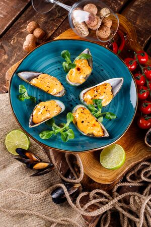 Large blue mussels on a blue plate on a wooden background, near the rope and products for cooking