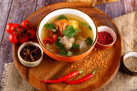 Uzbek shurpa soup in a bowl with two hot peppers