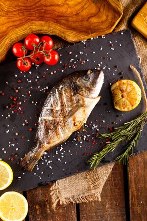 delicious roasted dorado or Gilt-head bream fish with lemon and orange slices, spices, and fresh rosemary on baking sheet, Reklamní fotografie