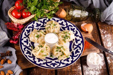 Georgian khinkali dumplings with meat, herbs and tomato hot sauce Satsebeli