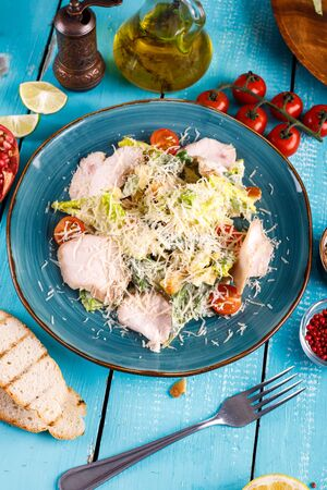 Caesar salad in a plate on the table next to vegetables Imagens