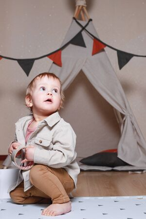 A child, a boy, is sitting and playing in a tent inside the house on a wooden background.