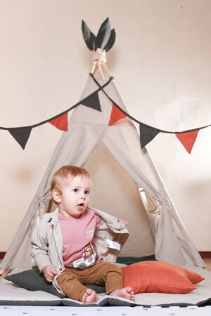A child, a boy, is sitting and playing in a tent inside the house on a wooden background. He is dressed in trousers and a shirt in a beige color scheme