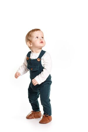 A one-year-old boy in a green jumpsuit on a white background