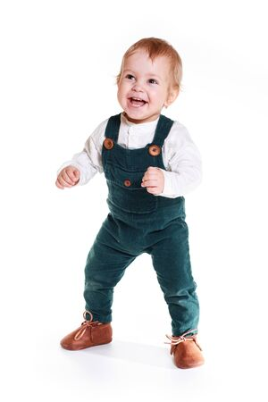 a cute one-year-old child stands in a White Studio. The boy has a happy expression on his face. He is dressed in a white shirt and overalls