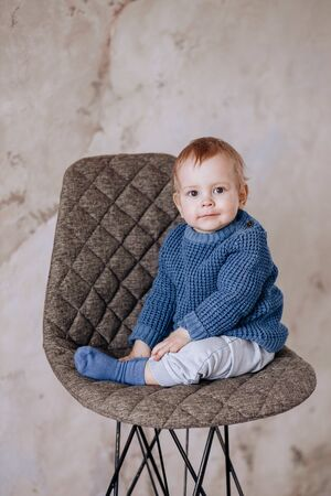 Cute Studio portrait of a one-year-old boy sitting on a chair. A boy with very large beautiful eyes. A boy in a blue sweater and beige pants